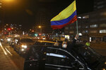 A supporter of former President Alvaro Uribe holding a national flag takes part in caravan to protest the Supreme Court decision to place Uribe under house arrest while it advances a witness tampering investigation against him, in Bogota, Colombia, Tuesday, Aug. 4, 2020. (AP Photo/Fernando Vergara)