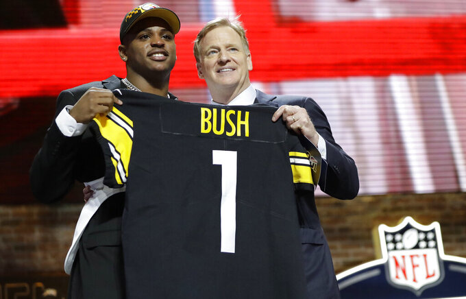 Michigan linebacker Devin Bush poses with NFL Commissioner Roger Goodell after the Pittsburgh Steelers selected Bush in the first round at the NFL football draft, Thursday, April 25, 2019, in Nashville, Tenn. (AP Photo/Mark Humphrey)