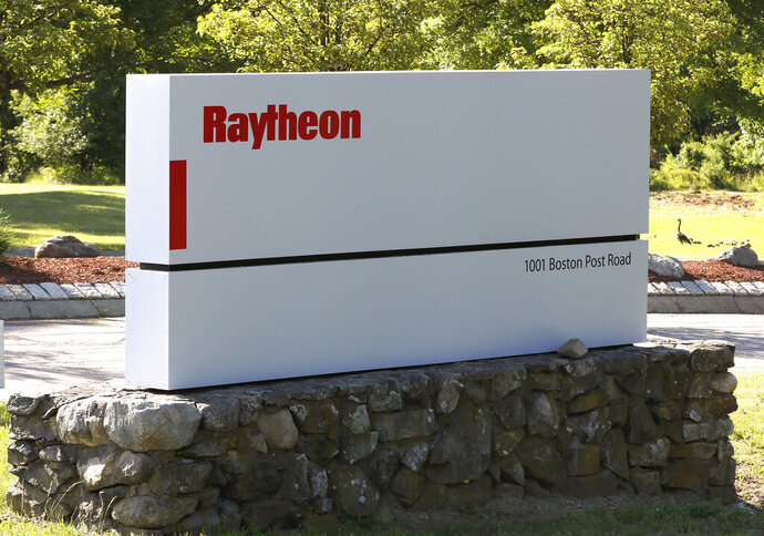 A sign stands at the road leading to the Raytheon facility in a Monday, June 10, 2019 photo, in Marlborough, Mass.Raytheon Technologies plans to eliminate more than 15,000 jobs this year in its corporate offices, jet engine-maker Pratt & Whitney and aviation and military equipment manufacturer Collins Aerospace. Chief Executive Officer Greg Hayes announced the revised job cut numbers Wednesday during a Morgan Stanley analysts conference.   (AP Photo/Bill Sikes, File)