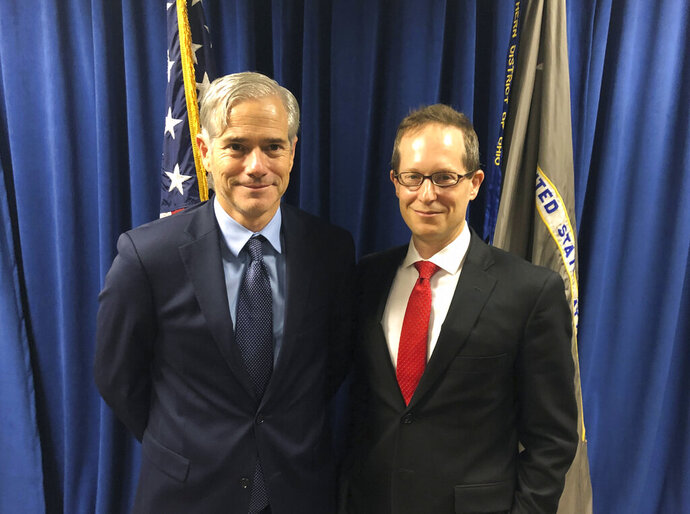 In this Tuesday, Oct. 29, 2018, photo David DeVillers, left, a veteran prosecutor confirmed this week by the U.S. Senate to become U.S. Attorney for southern Ohio, stands with current U.S. Attorney Benjamin C. Glassman in the federal prosecutor's offices in Cincinnati. Glassman, who steps down Friday, Nov. 1, discussed his hectic three years, including a deadly mass shooting this summer in Dayton, as head of the office during an interview with The Associated Press. (AP Photo/Dan Sewell)