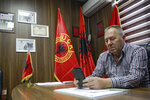 Hysni Gucati head of the War Veterans Organization of the Kosovo Liberation Army looks at a photo of his co-fighter former Kosovo Liberation Army commander Salih Mustafa after news of his arrest,  during an interview with The Associated Press, in Pristina, Thursday, Sept. 24, 2020. A special international court said Thursday that a former commander of the separatist fighters in Kosovo's 1998-1999 war has been arrested as part of a war crimes and crimes against humanity probe stemming from the conflict with Serbia. (AP Photo/Visar Kryeziu)