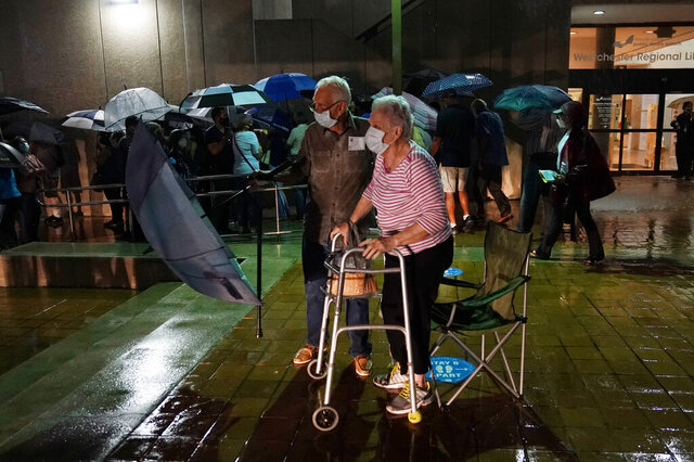 A couple stands in line as rain falls on voters waiting for the precinct to open, Monday, Oct. 19, 2020 in Miami. Florida begins in-person early voting in much of the state Monday. With its 29 electoral votes, Florida is crucial to both candidates in order to win the White House. (AP Photo/Lynne Sladky)