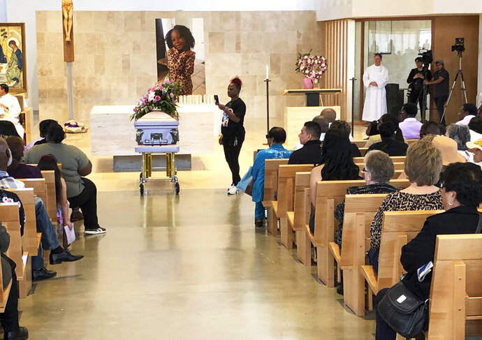 Mourners gather for the funeral service of Trinity Love Jones, the 9-year-old whose body was found this month stuffed in a duffel bag along an equestrian trail, at St. John Vianney Catholic Church in Hacienda Heights, Calif., Monday, March 25, 2019. The Hacienda Heights community where her body was found had embraced the child in death during the days she remained unidentified. A park worker found Trinity on March 5. A huge memorial sprang up at the site as community members heard about the case. She was identified the following weekend and prosecutors have since filed murder charges against her mother and the mother's boyfriend. (AP Photo/John Rogers)