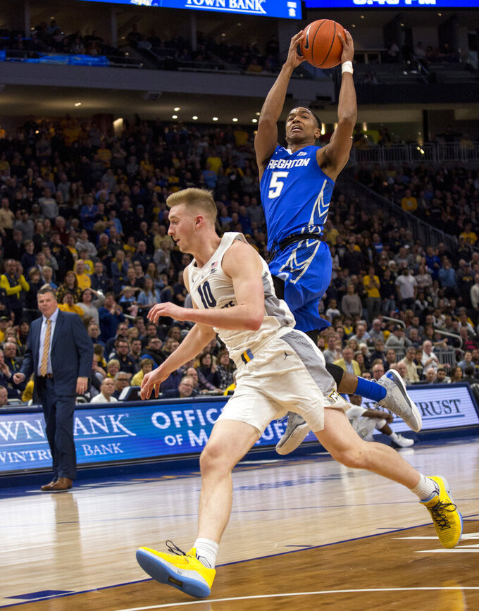 Creighton Ty-Shon Alexander, right, goes up for a basket against Marquette forward Sam Hauser, left, during the second half of an NCAA college basketball game Sunday, March 3, 2019, in Milwaukee. (AP Photo/Darren Hauck)