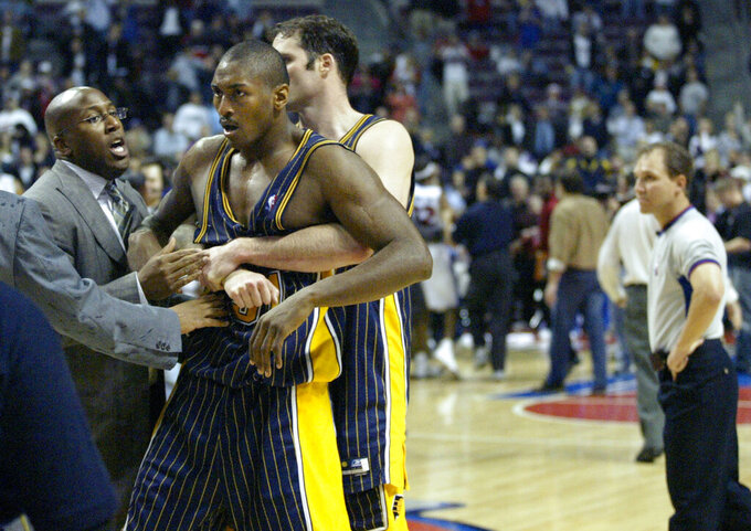 """FILE - Indiana Pacers' Ron Artest is restrained by Austin Croshere before being escorted off the court following their fight with the Detroit Pistons and fans on Nov. 19, 2004, in Auburn Hills, Mich. The famous """"Malice at the Palace"""" brawl, Caitlyn Jenner's reflections toward winning an Olympic gold medal and boxer Christy Martin's fight for her life outside the ring are some of the most pivotal sports moments highlighted in a new Netflix docuseries airing next month. The streaming service giant announced Tuesday, July 20, 2021, that the series """"UNTOLD"""" will premiere Aug. 10. (AP Photo/Duane Burleson, File)"""