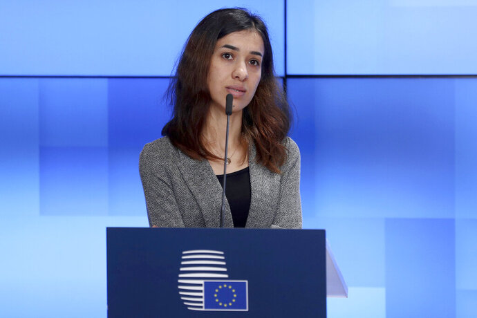 """FILE - In this Nov. 26, 2018, file photo, Nobel Peace Prize laureate Nadia Murad talks during a joint statement along with Nobel Peace Laureat Denis Mukwege and European Union Foreign Policy chief Federica Mogherini, at European Council's Europa building in Brussels.  Murad says the coronavirus pandemic has increased trafficking of women and gender-based violence, leaving the health and safety of women """"on the line.""""  The 27-year-old activist, who was forced into sexual slavery by Islamic State fighters in Iraq, says curfews, lockdowns and travel restrictions imposed by governments to slow the spread of the virus """"have had unintended consequences on women worldwide."""" (AP Photo/Francisco Seco, File)"""