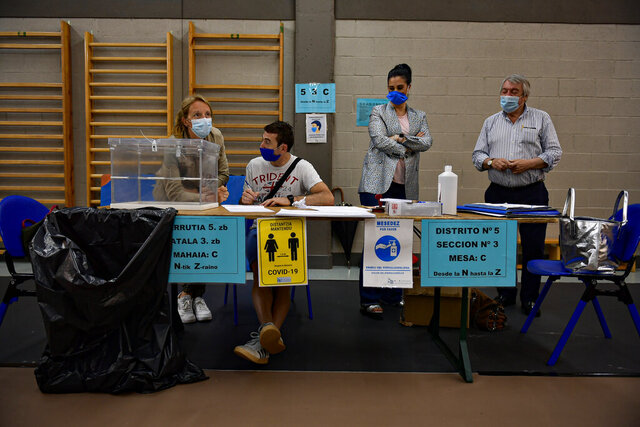 Polling station staff wear face masks to help curb the spread of the coronavirus while waiting for people to vote in the Basque regional election in the village of Durango, northern Spain, Sunday, July 12, 2020. Basque authorities display special rules for protection against the coronavirus. (AP Photo/Alvaro Barrientos)