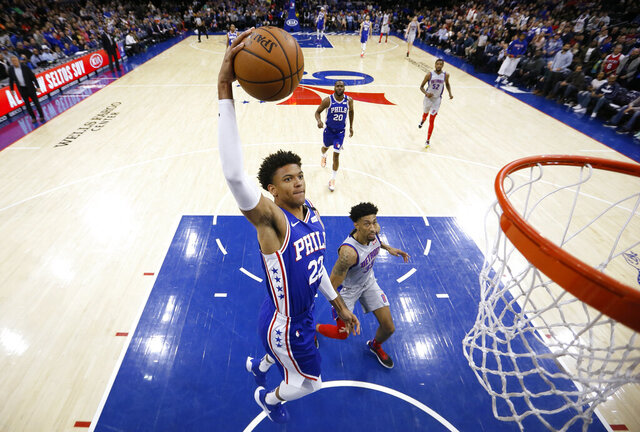 Philadelphia 76ers' Matisse Thybulle (22) goes up for a dunk past Detroit Pistons' Christian Wood (35) during the first half of an NBA basketball game, Wednesday, March 11, 2020, in Philadelphia. (AP Photo/Matt Slocum)