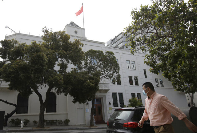 A man walks across the street from the Chinese Consulate in San Francisco, Thursday, July 23, 2020. The Chinese consulate in San Francisco is harboring a Chinese researcher who the FBI says lied about her military background. (AP Photo/Jeff Chiu)