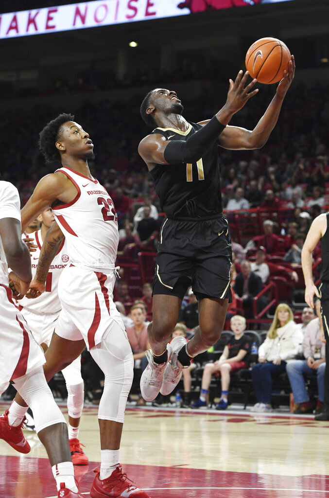 Vanderbilt forward Simisola Shittu (11) drives past Arkansas defender Gabe Osabuohien (22) during the second half of an NCAA college basketball game, Tuesday, Feb. 5, 2019 in Fayetteville, Ark. (AP Photo/Michael Woods)