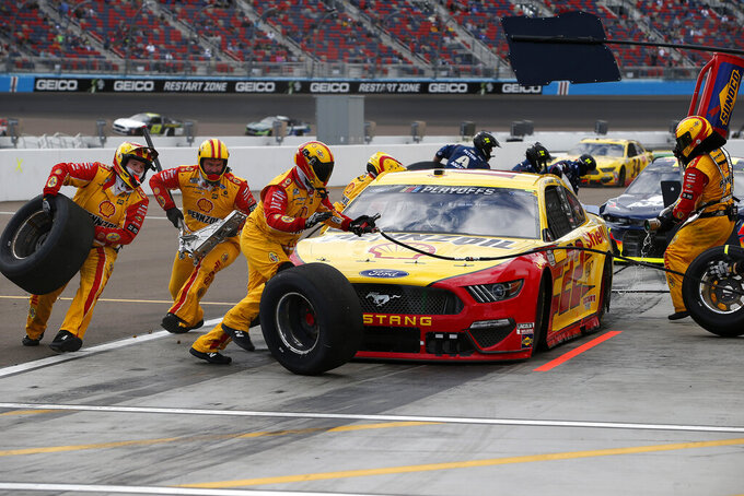 The pit crew for Joey Logano (22) scramble around the car on a pit stop during a NASCAR Cup Series auto race at Phoenix Raceway, Sunday, Nov. 8, 2020, in Avondale, Ariz. (AP Photo/Ralph Freso)