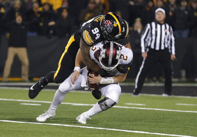 Iowa defensive end A.J. Epenesa, top, sacks Minnesota quarterback Tanner Morgan during the second half of an NCAA college football game, Saturday, Nov. 16, 2019, in Iowa City, Iowa. (AP Photo/Matthew Putney)