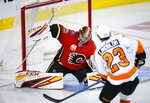 Philadelphia Flyers' Oskar Lindblom, right, has his shot deflected by Calgary Flames goalie David Rittich during the second period of an NHL hockey game Tuesday, Oct. 15, 2019, in Calgary, Alberta. (Jeff McIntosh/The Canadian Press via AP)
