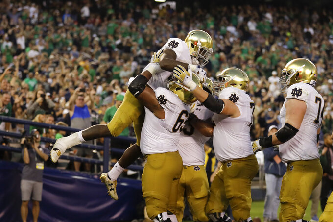 Notre Dame running back Dexter Williams, above, is lifted by teammate long snapper Michael Vinson after scoring a touchdown during the first half of an NCAA college football game against Navy Saturday, Oct. 27, 2018, in San Diego. (AP Photo/Gregory Bull)