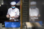 A chef wearing a face mask prepares food at a shop on a pedestrian shopping street in Beijing, Saturday, May 16, 2020. According to official data released on Saturday India's confirmed coronavirus cases have surpassed China's. (AP Photo/Mark Schiefelbein)