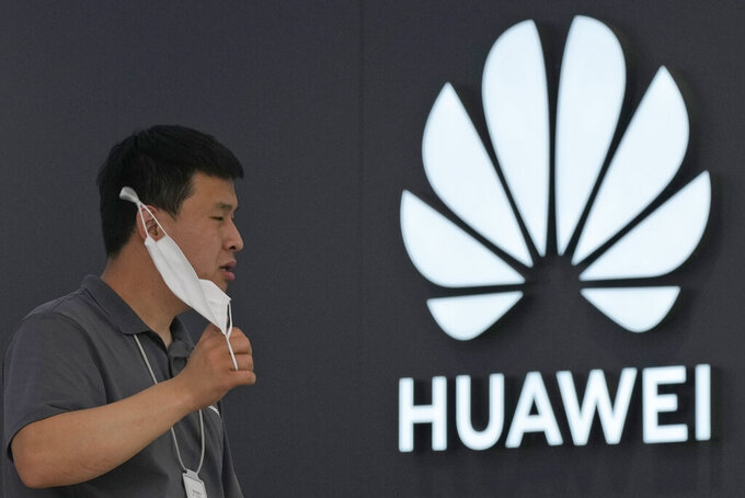A worker waits for customers inside a Huawei store in Beijing on Wednesday, June 2, 2021. Huawei is launching its own HarmonyOS mobile operating system on its handsets as it adapts to losing access to Google mobile services two years ago after the U.S. put the Chinese telecommunications company on a trade blacklist. (AP Photo/Ng Han Guan)
