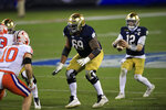 Notre Dame offensive lineman Aaron Banks (69) protects quarterback Ian Book (12) from Clemson linebacker Baylon Spector (10) during the second half of the Atlantic Coast Conference championship NCAA college football game, Saturday, Dec. 19, 2020, in Charlotte, N.C. (AP Photo/Brian Blanco)