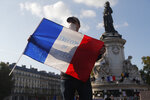 A demonstrator holds a French flag with the slogan