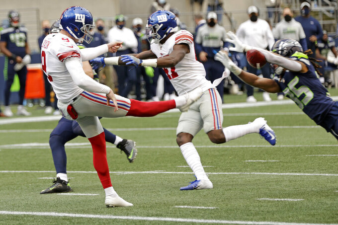 New York Giants punter Riley Dixon has a punt blocked by Seattle Seahawks cornerback Ryan Neal, right, for a safety during the first half of an NFL football game, Sunday, Dec. 6, 2020, in Seattle. (AP Photo/Larry Maurer)