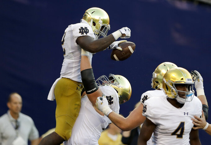 Notre Dame offensive lineman Robert Hainsey, below, raises teammate running back Dexter Williams after a touchdown by Williams during the first half of an NCAA college football game against Navy Saturday, Oct. 27, 2018, in San Diego. (AP Photo/Gregory Bull)