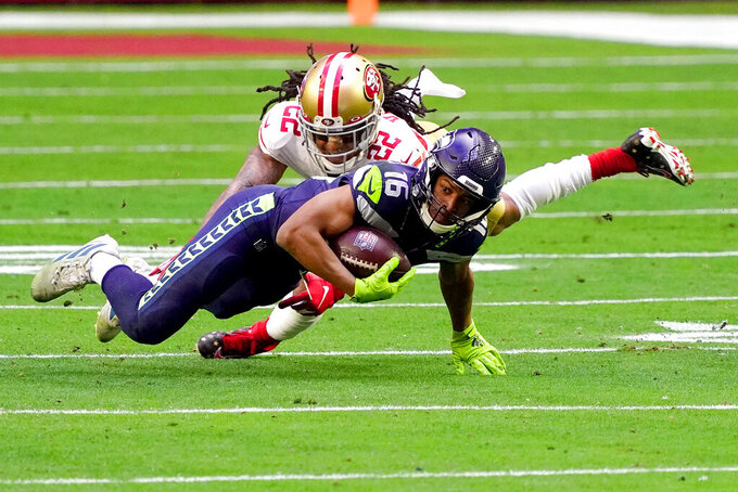 Seattle Seahawks cornerback Quinton Dunbar (22) tackles Seattle Seahawks wide receiver Tyler Lockett (16) during the first half of an NFL football game, Sunday, Jan. 3, 2021, in Glendale, Ariz. (AP Photo/Rick Scuteri)