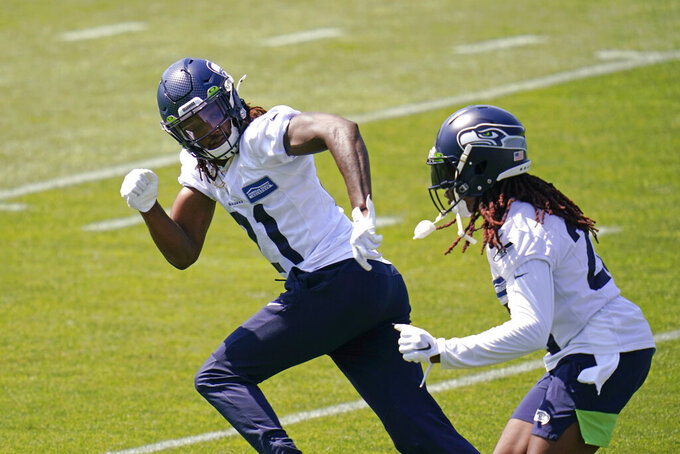Seattle Seahawks cornerback Tre Flowers, left, is trailed by cornerback Shaquill Griffin Thursday, Aug. 13, 2020, as they take part in a practice during an NFL football training camp in Renton, Wash. (AP Photo/Elaine Thompson)