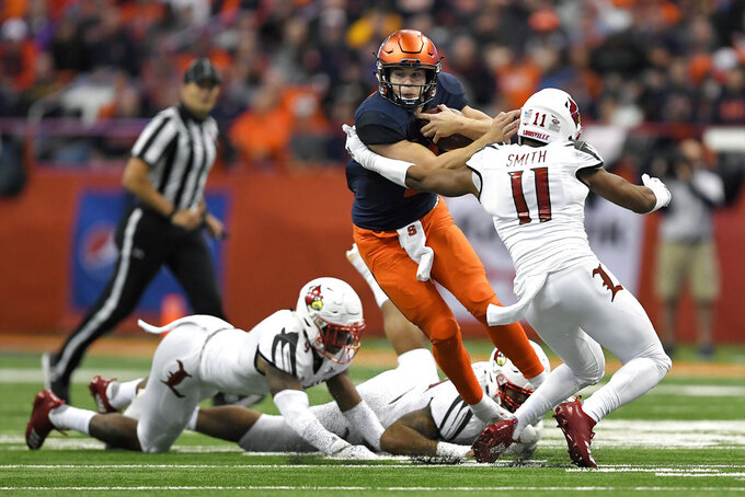 Syracuse quarterback Eric Dungey, left, eludes Louisville safety Dee Smith (11) during the first half of an NCAA college football game in Syracuse, N.Y., Friday, Nov. 9, 2018. (AP Photo/Adrian Kraus)