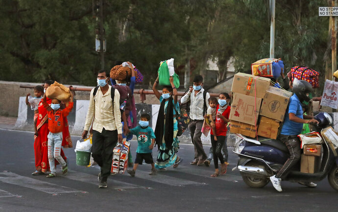 A migrant worker family crosses a street as they leave city to go back to their villages during a nationwide lockdown to curb the spread of new coronavirus in New Delhi, India, Thursday, May 21, 2020. India's lockdown was imposed on March 25 and has been extended several times. On May 4, India eased lockdown rules and allowed migrant workers to travel back to their homes, a decision that has resulted in millions of people being on the move for the last two weeks. (AP Photo/Manish Swarup)