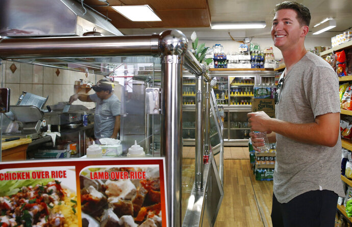 FILE - In this Aug. 25, 2016, file photo, minor league pitcher Gary Cornish banters with employees as he waits for his regular takeout order, iced coffee, a breakfast burrito and a turkey sandwich to go for $13.50 from Mingo's Sandwich Factory, a corner bodega he frequents near the team's hotel in the Brooklyn neighborhood of New York. Major League Baseball is raising the minimum salary for minor league players in 2021, according to a memo sent from the commissioner's office to all 30 teams obtained by The Associated Press. (AP Photo/Kathy Willens, File)