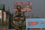 An Indian paramilitary soldier stands guard at a temporary checkpoint in Srinagar, Indian controlled Kashmir, Friday, Sept. 3, 2021. Indian authorities cracked down on public movement and imposed a near-total communications blackout in disputed Kashmir on Thursday after the death of Syed Ali Geelani, a top separatist leader who became the emblem of the region's defiance against New Delhi. (AP Photo/ Dar Yasin)