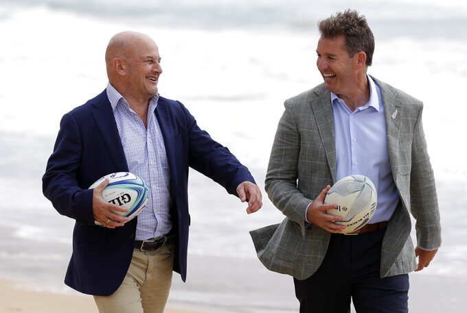 New Zealand Rugby Chief Executive Mark Robinson, right, and Rugby Australia interim Chief Executive Rob Clarke pose for photos on Manly Beach in Sydney, Friday, Nov. 13, 2020. Clubs from Australia and New Zealand will stage a six-week trans-Tasman tournament next year following their respective domestic Super Rugby competitions. (AP Photo/Rick Rycroft)