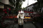 A damaged statue taken from a church forms part of barricade created by anti-government protesters, in Santiago, Chile, Friday, Nov. 8, 2019. Chile's president on Thursday announced measures to increase security and toughen sanctions for vandalism following three weeks of protests that have left at least 20 dead. (AP Photo/Luis Hidalgo)