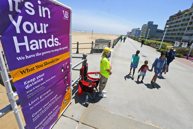 Beach Ambassador Kyla Miller, left, stands ready to help visitors to the oceanfront Friday, May 22, 2020, in Virginia Beach, Va. Virginia Gov. Ralph Northam lifted restrictions and opened the beachfront beginning Friday. (AP Photo/Steve Helber)