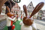 Human-sized wooden figures representing Easter bunnies playing music stand in front of Michelstadt's historic town hall, as they do every year, to spread Easter atmosphere in Michelstadt, Germany, Thursday, April 1, 2021. However, the popular meeting place in the heart of the town in the Odenwald was almost deserted on Thursday morning due to the pandemic. (Frank Rumpenhorst/dpa via AP)