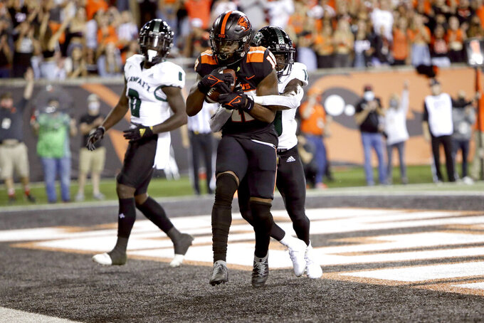 Oregon State wide receiver Zeriah Beason (18) scores on a pass as Hawaii defensive back Cortez Davis (18) tries to intercept him during the first half of an NCAA college football game Saturday, Sept. 11, 2021, in Corvallis, Ore. (AP Photo/Amanda Loman)