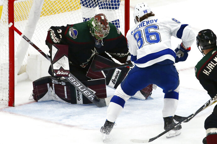 Arizona Coyotes goaltender Antti Raanta, left, makes a save on a shot by Tampa Bay Lightning right wing Nikita Kucherov (86) during the first period of an NHL hockey game Saturday, Feb. 22, 2020, in Glendale, Ariz. (AP Photo/Ross D. Franklin)