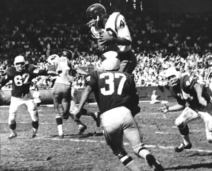 FILE - In this Oct. 15, 1962, file photo, Bobby Mitchell, of the Washington Redskins, jumps to haul in a pass from quarterback Norman Snead in the second period of their NFL football game against the St. Louis Cardinals in St. Louis. Mitchell, the speedy late 1950s and '60s NFL offensive star the Cleveland Browns and the Redskins, has died. He was 84. The Pro Football Hall of Fame said Sunday night, April 5, 2020, that Mitchell's family said he died in the afternoon. (AP Photo/Fred Waters, File)