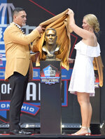 Former NFL player Kevin Mawae, left, unveils a bust of himself with his presenter and wife, Tracy Mawae, during the induction ceremony at the Pro Football Hall of Fame, Saturday, Aug. 3, 2019, in Canton, Ohio. (AP Photo/David Richard)