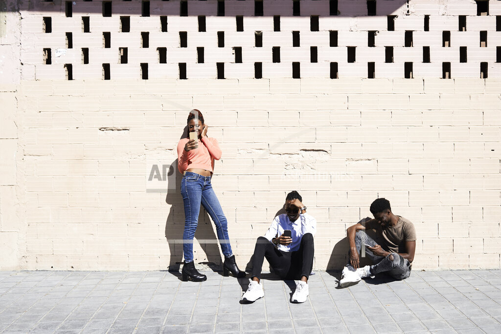 Three friends using smartphones outdoors ignoring each other