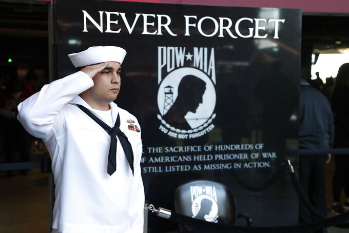 U.S. Navy MM3 Paul Alvaraeo, of Fort Worth Texas, salutes in front of the POW-MIA memorial was at Mercedes-Benz Stadium during the national anthem before the first half of an NFL football game between the Atlanta Falcons and the Seattle Seahawks, Sunday, Oct. 27, 2019, in Atlanta. (AP Photo/John Bazemore)