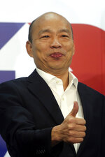 Han Kuo-yu of the Nationalist Party shows a thumbs-up during a media event announcing his campaign logo in Taipei, Taiwan, Thursday, Nov. 14, 2019. The China-friendly opposition candidate in Taiwan's upcoming presidential election is urging Hong Kong to adopt universal suffrage as the best way of stemming months of anti-government protests. (AP Photo/Chiang Ying-ying)