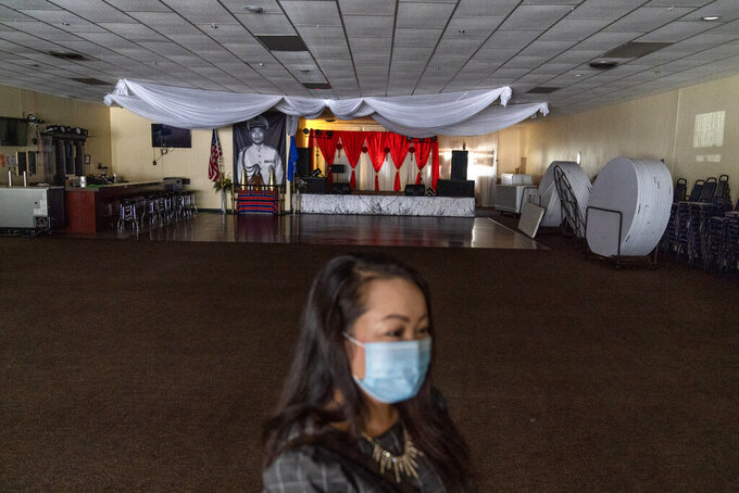 "Businesswoman and city councilor, Maiyoua Thao, 43, stands in the virus-shuttered banquet hall that serves the area's 5,000 Hmong immigrants, Aug. 19, 2020, in Appleton, Wis. Thao, a Hmong refugee from Laos, was initially drawn to the President Donald Trump mythology. She read his books and stayed in his hotel. But his administration has irked her by slashing the admission of refugees this year. She refuses to weigh in on national politics, saying that doing so could alienate the residents she serves. ""I just want to see us Americans continue to be powerful and to be the heroes to the world."" (AP Photo/David Goldman)"