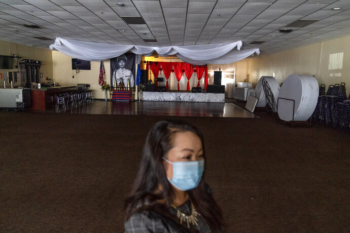 Businesswoman and city councilor, Maiyoua Thao, 43, stands in the virus-shuttered banquet hall that serves the area's 5,000 Hmong immigrants, Aug. 19, 2020, in Appleton, Wis. Thao, a Hmong refugee from Laos, was initially drawn to the President Donald Trump mythology. She read his books and stayed in his hotel. But his administration has irked her by slashing the admission of refugees this year. She refuses to weigh in on national politics, saying that doing so could alienate the residents she serves.