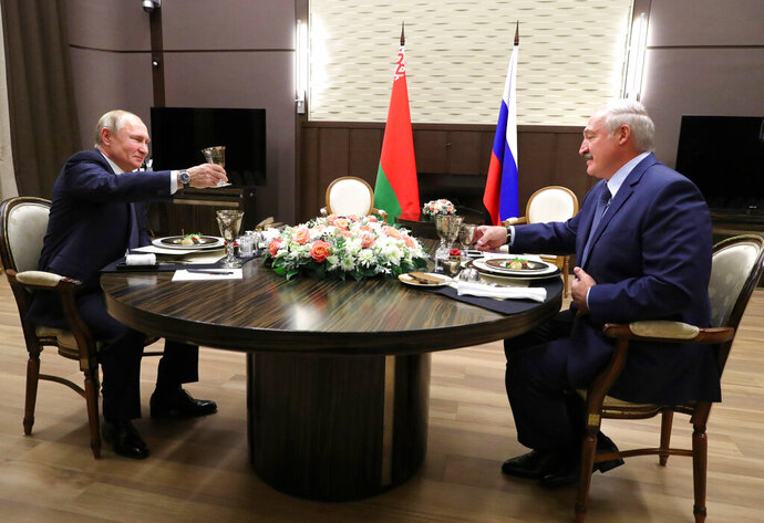 Russian President Vladimir Putin, left, and Belarusian President Alexander Lukashenko raise a toast during their meeting in the Black sea resort of Sochi, Russia, Saturday, Dec. 7, 2019. Leaders of Russia and Belarus sat down for talks Saturday on deepening ties between the two allies — a meeting that triggered a protest in the Belarusian capital. More than 1,000 opposition demonstrators rallied in Minsk to protest closer integration with Russia, which they fear could erode the post-Soviet independence of the nation of 10 million. (Mikhail Klimentyev, Sputnik, Kremlin Pool Photo via AP)