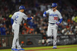 Los Angeles Dodgers' Cody Bellinger (35) is congratulated as he rounds the bases by third base coach Dino Ebel (12) after hitting a solo home run against the Colorado Rockies during the fourth inning of a baseball game Friday, Sept. 27, 2019, in San Francisco. (AP Photo/Tony Avelar)