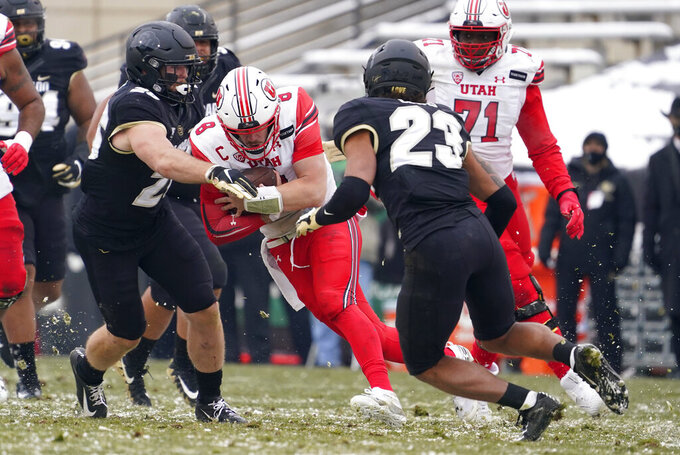 Utah quarterback Jake Bentley, center, is stopped after a short gain by Colorado linebacker Carson Wells, left, and safety Isaiah Lewis in the second half of an NCAA college football game Saturday, Dec. 12, 2020, in Boulder, Colo. Utah won 38-21. (AP Photo/David Zalubowski)