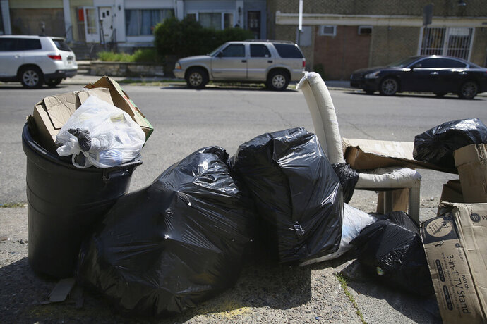 FILE— Bags of garbage sit along the street before being picked up in Philadelphia's Ogontz section in this file photo from May 13, 2020. Households are generating more trash as people stay home during the coronavirus pandemic.  (Tim Tai/The Philadelphia Inquirer via AP, File)