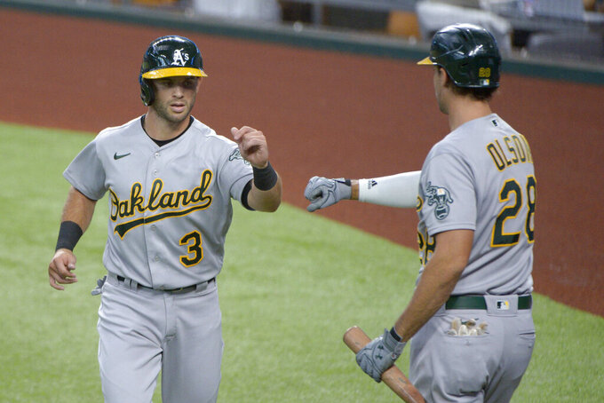 Oakland Athletics' Tommy La Stella (3) is greeted by Matt Olson (28) after scoring a run in the first inning of a baseball game against the Texas Rangers in Arlington, Tex, Sunday, Sept. 13, 2020. (AP Photo/Matt Strasen)