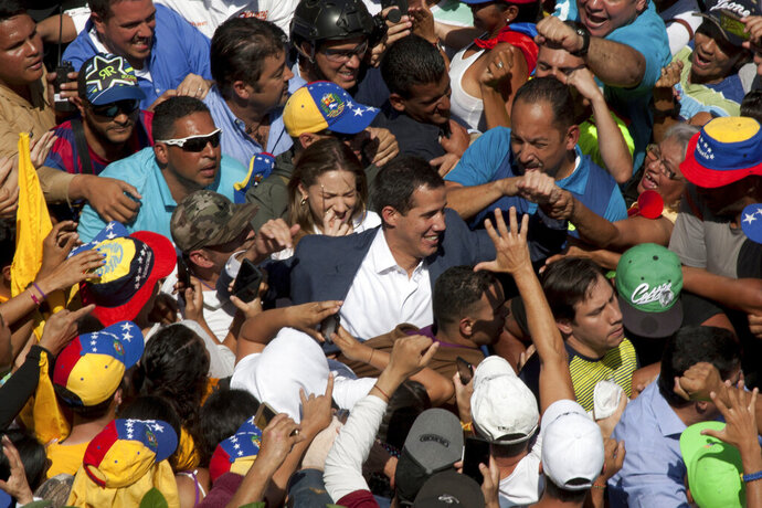 Venezuelan opposition leader Juan Guaido, center, who has declared himself the interim president of Venezuela, greets supporters as he arrives at a demonstration demanding the resignation of President Nicolas Maduro, in Caracas, Venezuela, Saturday, Feb. 2, 2019. Momentum is growing for Venezuela's opposition movement led by Guaido, who has called supporters back into the streets for nationwide protests Saturday, escalating pressure on Maduro to step down.(AP Photo/Juan Carlos Hernandez)