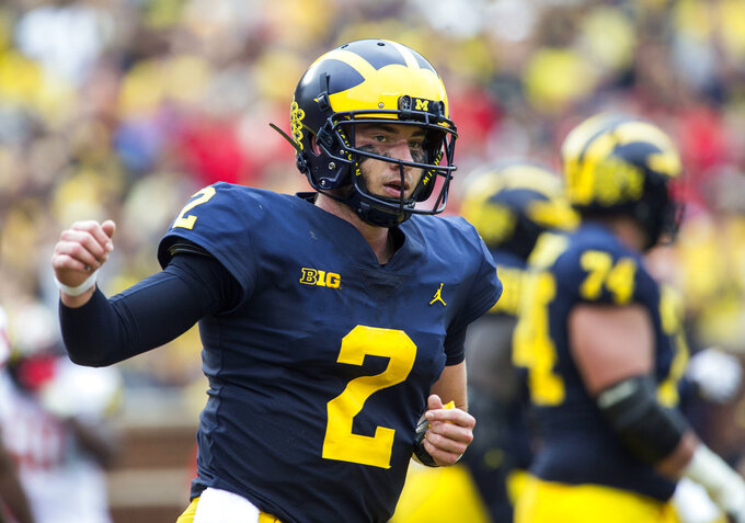 FILE - In this Saturday, Oct. 6, 2018, file photo, Michigan quarterback Shea Patterson (2) reacts after scoring a touchdown in the second quarter of an NCAA college football game against Maryland in Ann Arbor, Mich. No. 12 Michigan is undefeated since opening with a loss at Notre Dame, building momentum and confidence while waiting for its next opportunity to earn an impressive win. They won't have to wait much longer. No. 15 Wisconsin will come to play under the lights Saturday night at the Big House in what may prove to be a pivotal game in the conference's championship race.  (AP Photo/Tony Ding, File)